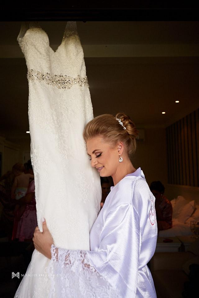 noiva de roupão de olhos fechados abraçando o vestido na varanda do hotel do making of