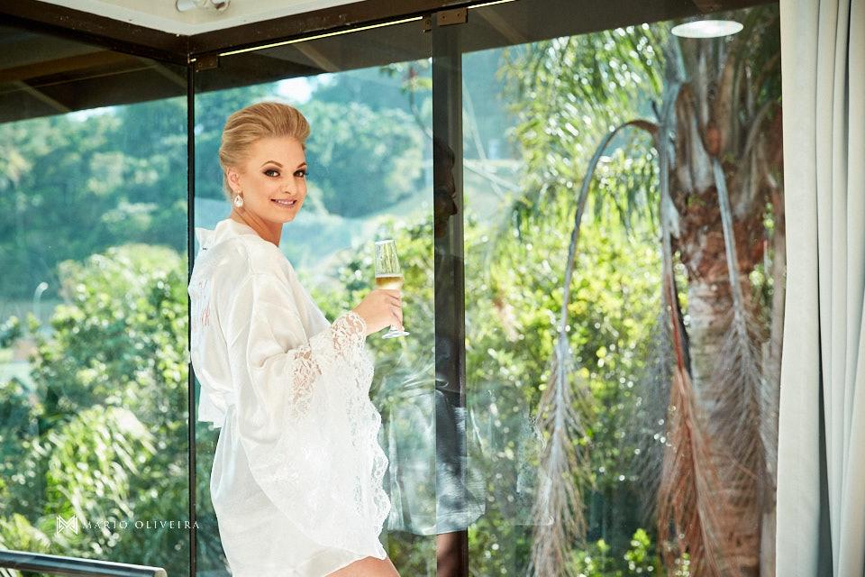 noiva de roupão em frente a janela segurando uma taça de espumante no hotel do making of