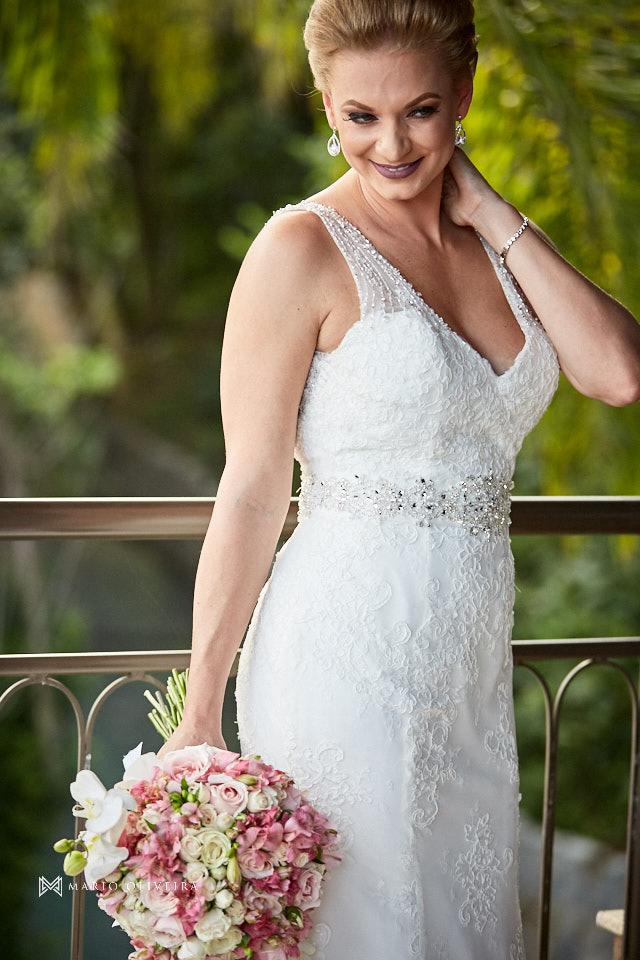 retrato da noiva em pé sorrindo segurando o buque e com a mão no pescoço