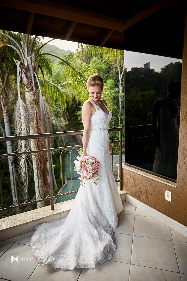 retrato da noiva em pé sorrindo segurando o buque