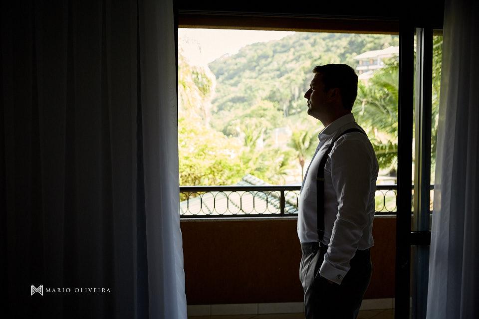 noivo em frente a janela infinity blue resort balneario camboriu com as mãos nos bolsos