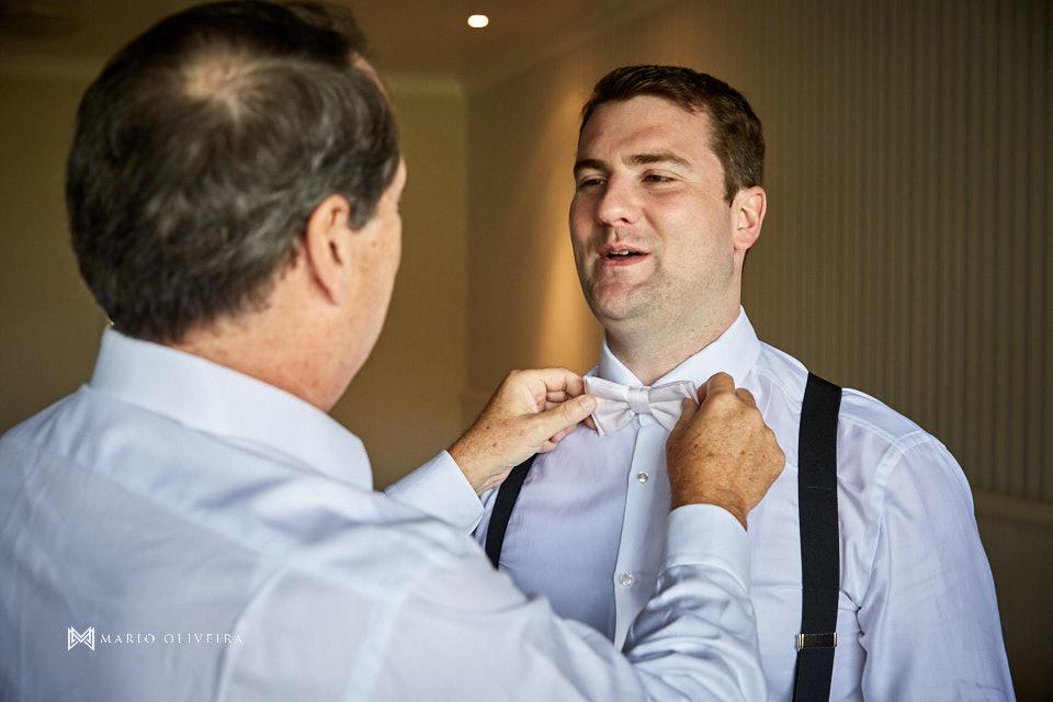 pai do noivo ajustando gravata borboleta do noivo