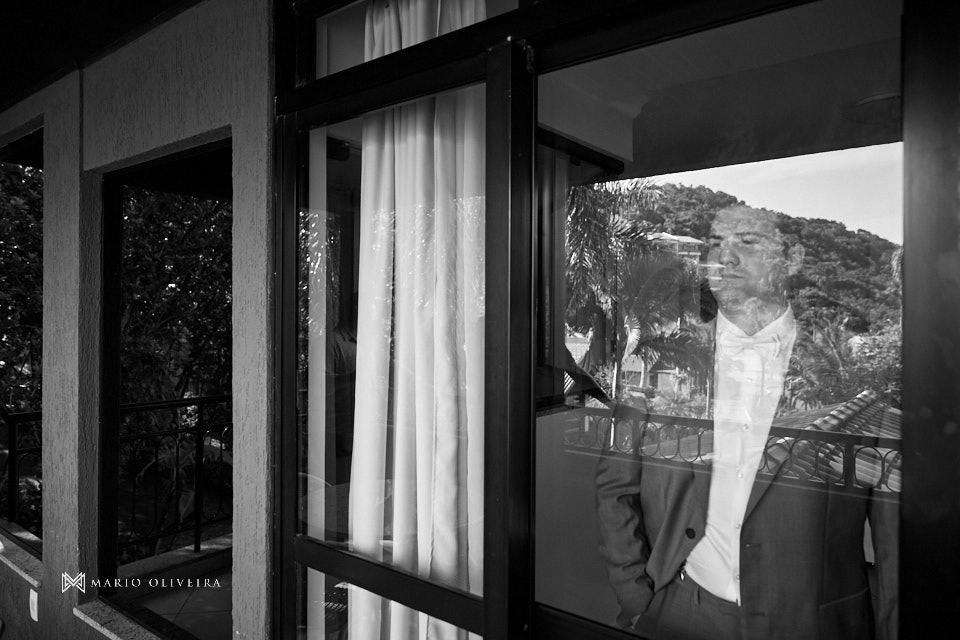 noivo pronto atras da janela da varanda do infinity blue resort balneario camboriu com o reflexo das arvores no vidro