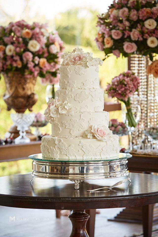 bolo de casamento com quatro andares e mesa de doces ao fundo