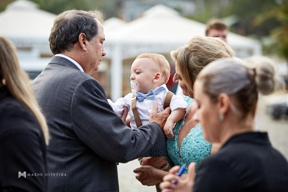 pai do noivo pegando bebe do colo da mãe da noiva