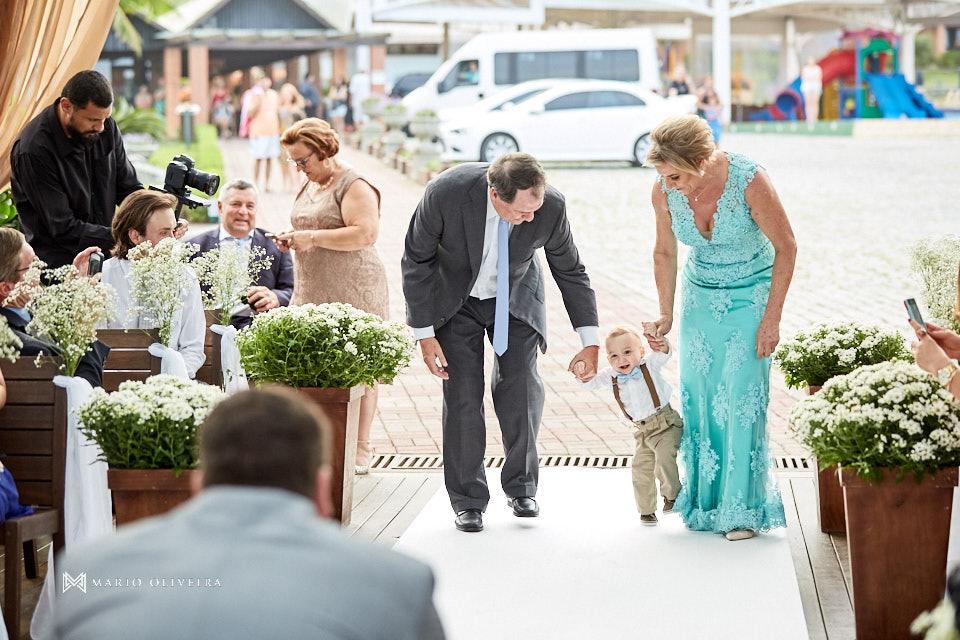 Pai do noivo e mãe da noiva entrando para cerimonia de casamento de mão dadas com um bebe de gravata borboleta e suspensorio