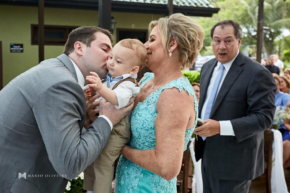 noivo beijando bebe no colo da mão da noiva com seu pai ao fundo