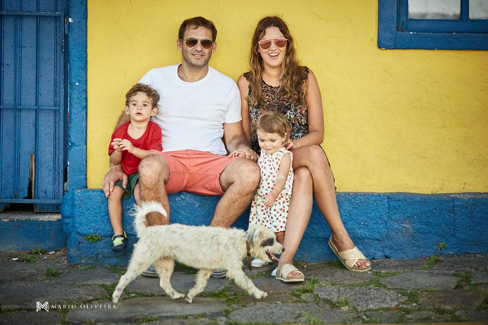 familia sentada se divertindo com um cachorro passando na frente