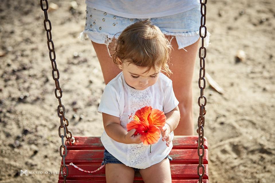 menina no balanço brincando com uma flor