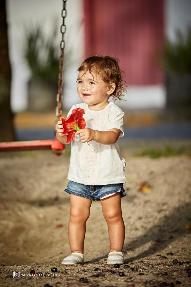 menina brincando no parquinho com uma flor na mão