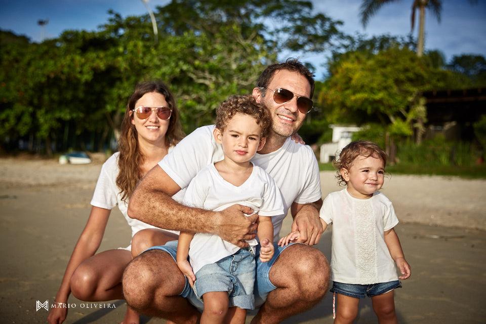 familia na praia se divertindo, pai e mão com filhos sorirndo