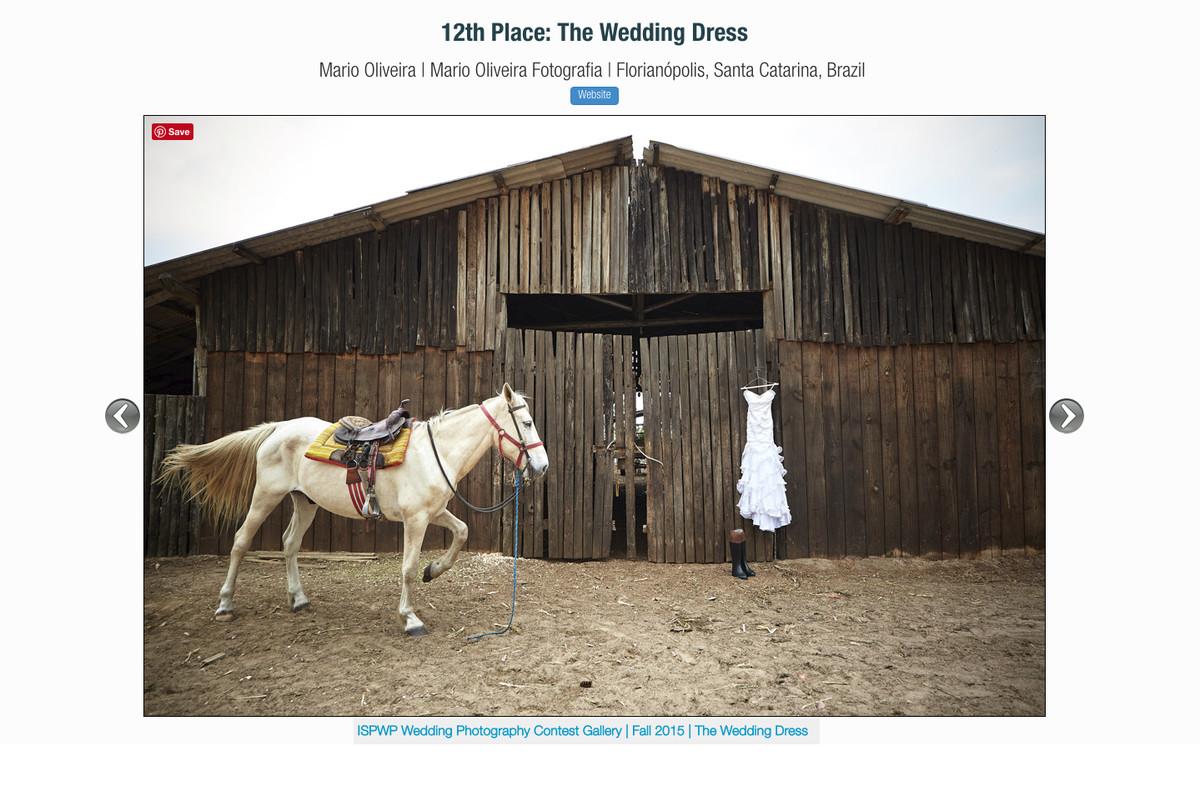 foto premiada na ISPWP Com o vestido da noiva em frente a um celeiro e um cavalo proximo