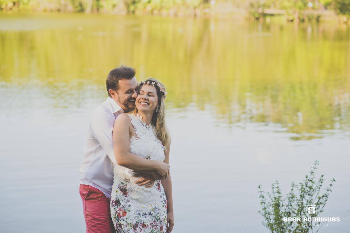 casal na beira do lago, noivo beijando a noiva no parque da cidade em São José dos Campos