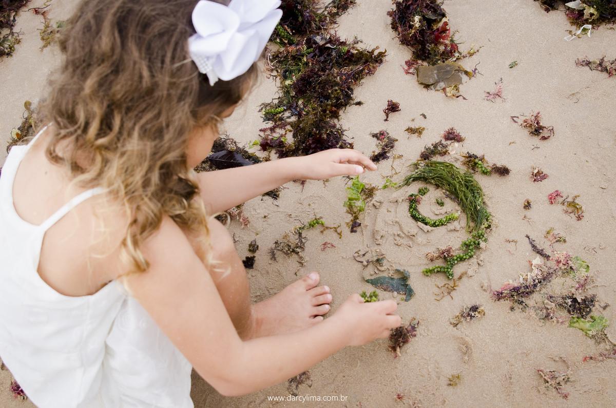 filha mais nova pega algas do mar para fazer um boneco de seu irmão