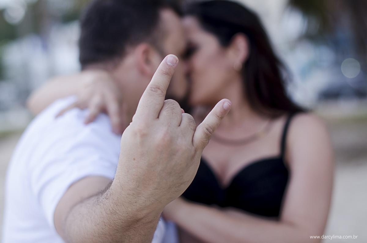 beijo do casal e o pai fazendo um sinal de rock and Roll