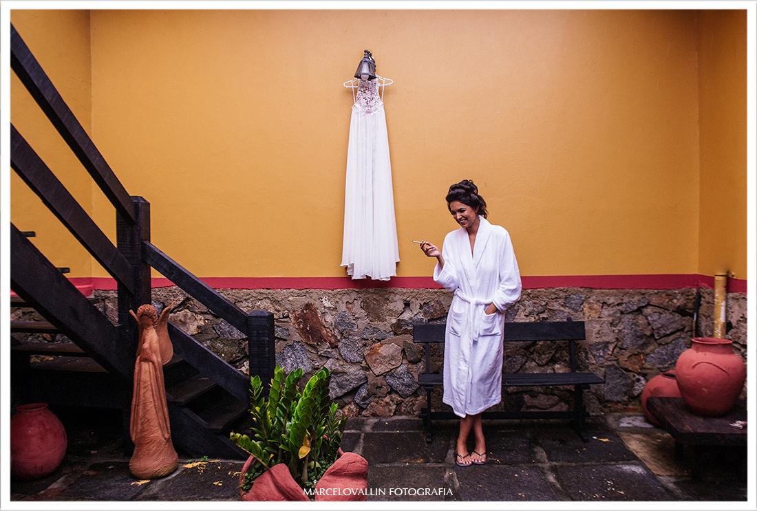 Fotografia da Noiva ao lado do vestido de noiva na pousada tanto mar