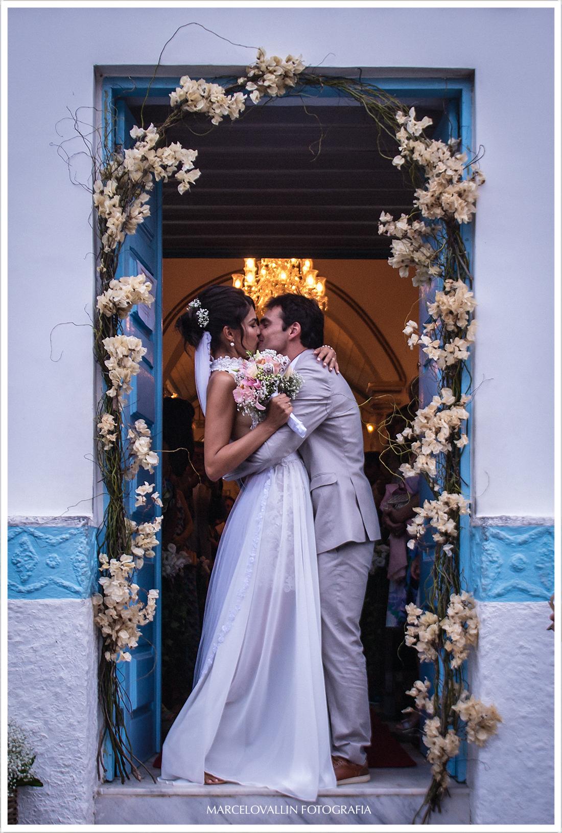 Noivos se beijando na porta da Igreja