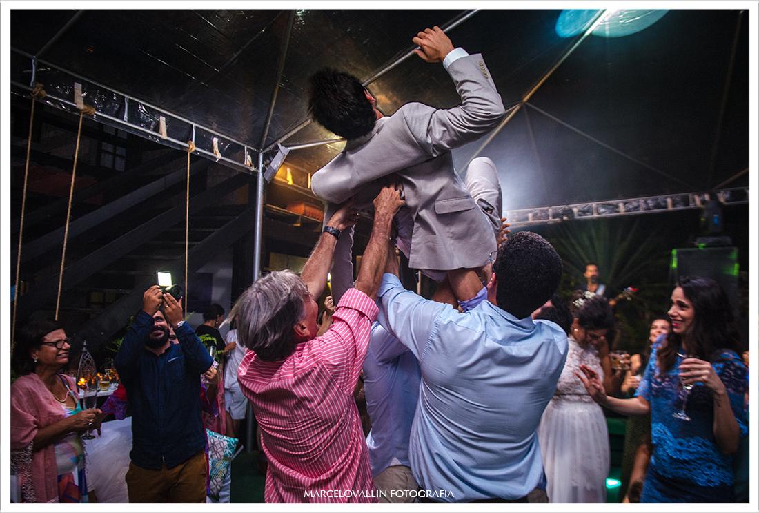 Amigos jogando noivo para o alto em festa de casamento