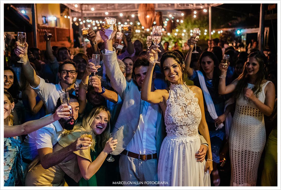 Foto dos noivos fazendo um brinde com amigos - Arraial do cabo