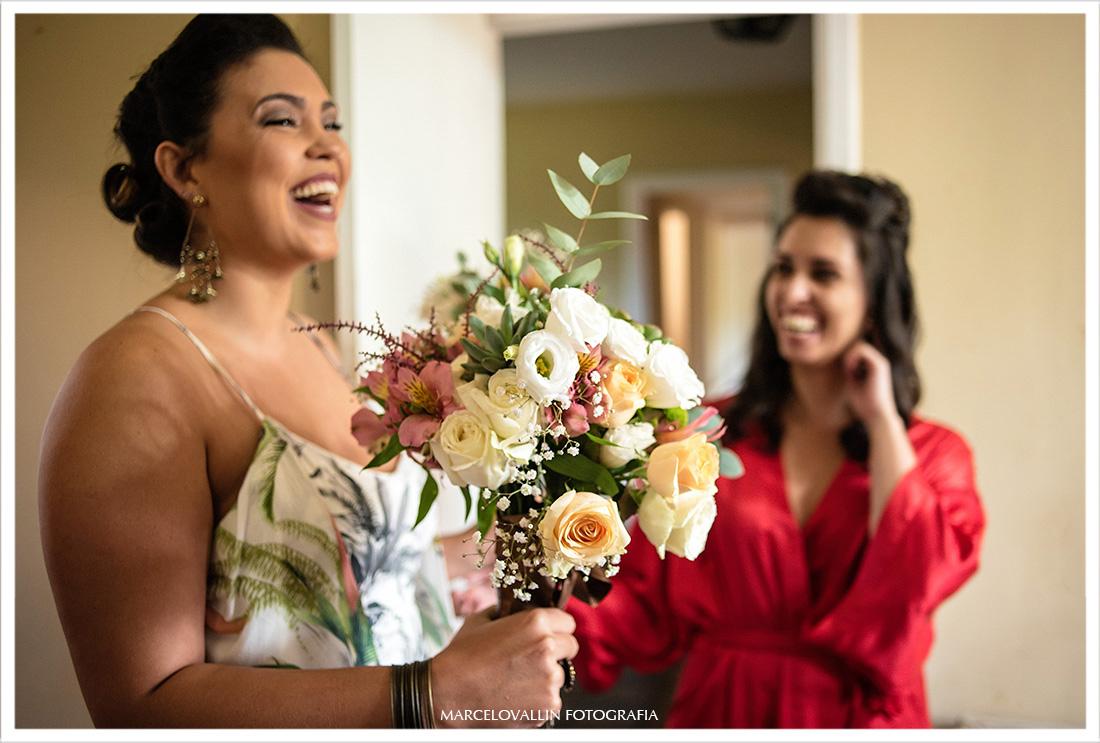 Madrinha sorrindo e entregando Buquê para noiva