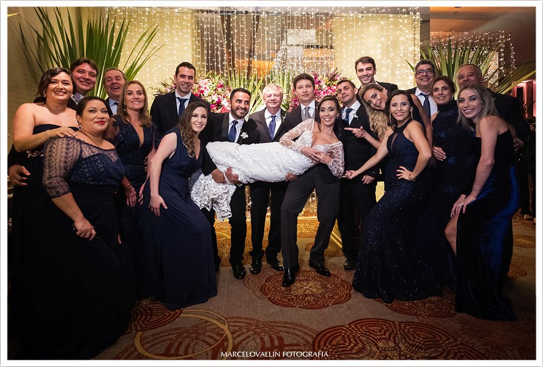 Fotografia da noiva no colo dos padrinhos