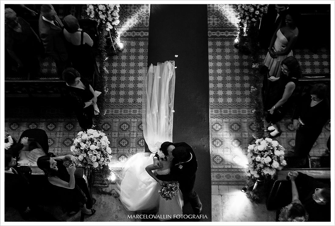 Fotografia dos noivos se beijando na saída da Igreja São José