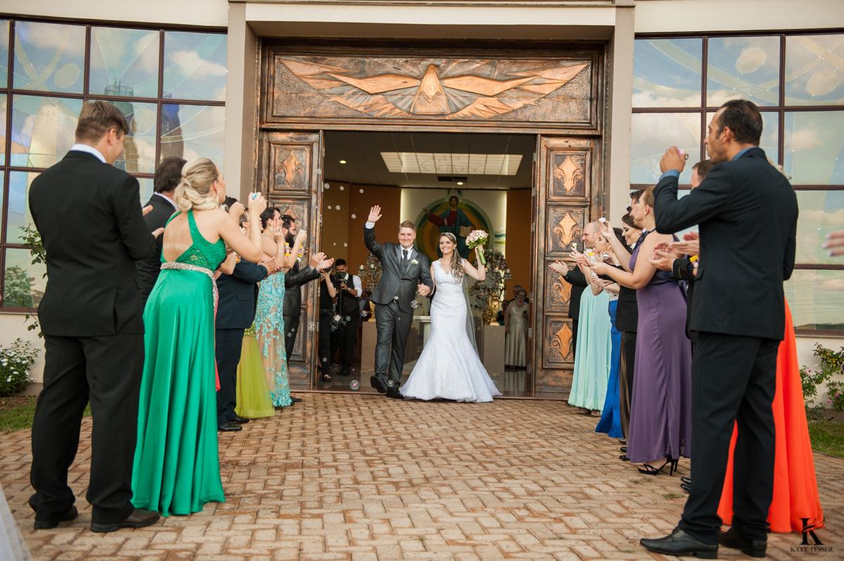 cerimonia de casamento em quedas do iguaçu, noivo de terno e noiva com vestido branco e buquet na igreja matriz saida dos noivos com o beijo e chuva de arroz fotografo katy tesser