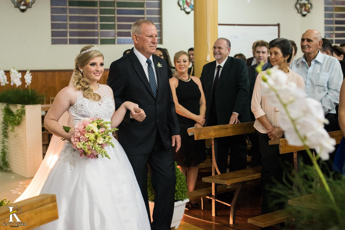 cerimonia de casamento heloisa e isaias em coronel vivida parana a entrada da noiva com vestido branco e buquet conduzida pelo pai fotografo katy tesser