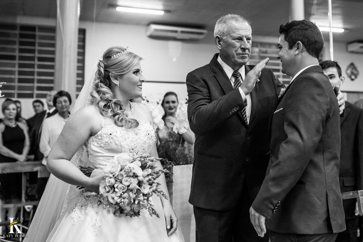 cerimonia de casamento heloisa e isaias em coronel vivida parana entrada da noiva com vestido branco e buquet seu pai cumprimenta o noivo e entrega sua filha fotografo katy tesser