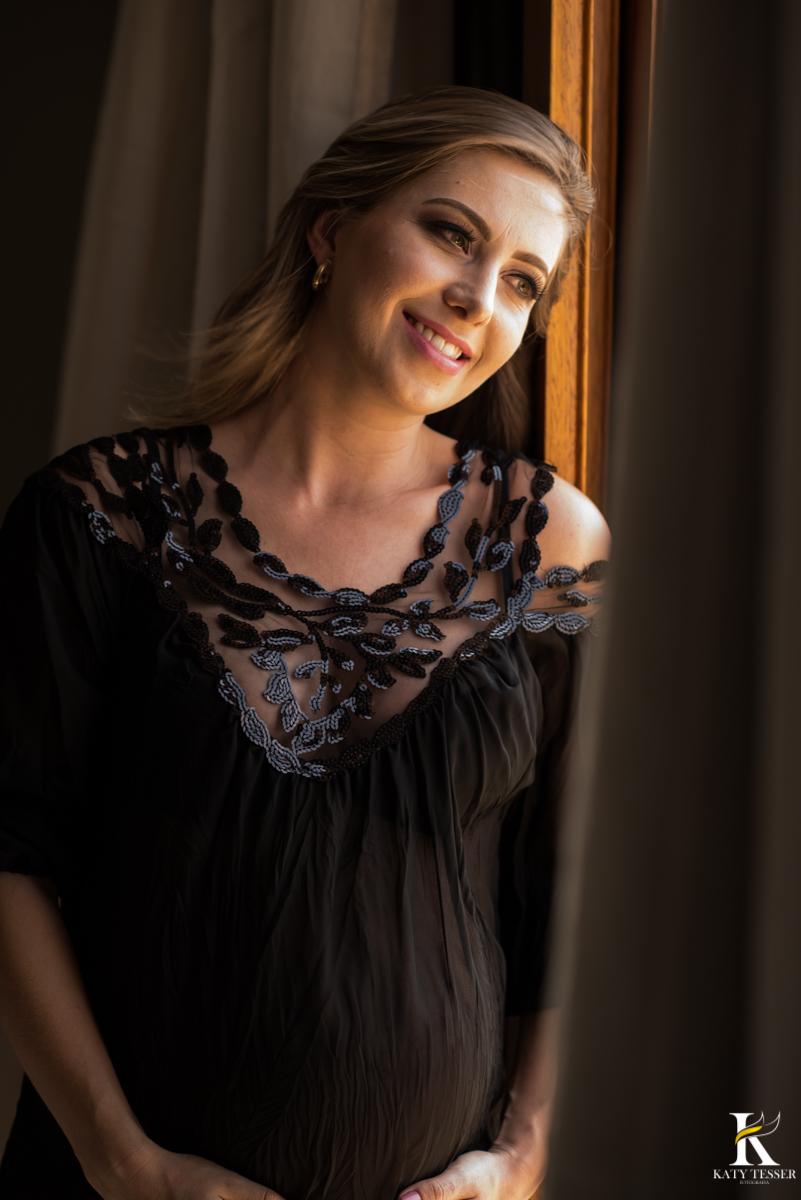 book da gestante juliana em pé próximo a janela foto katy tesser fotografa paraná