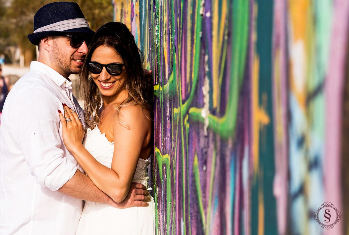 casal de noivos abraçados em frente de parede pichada floripa sc