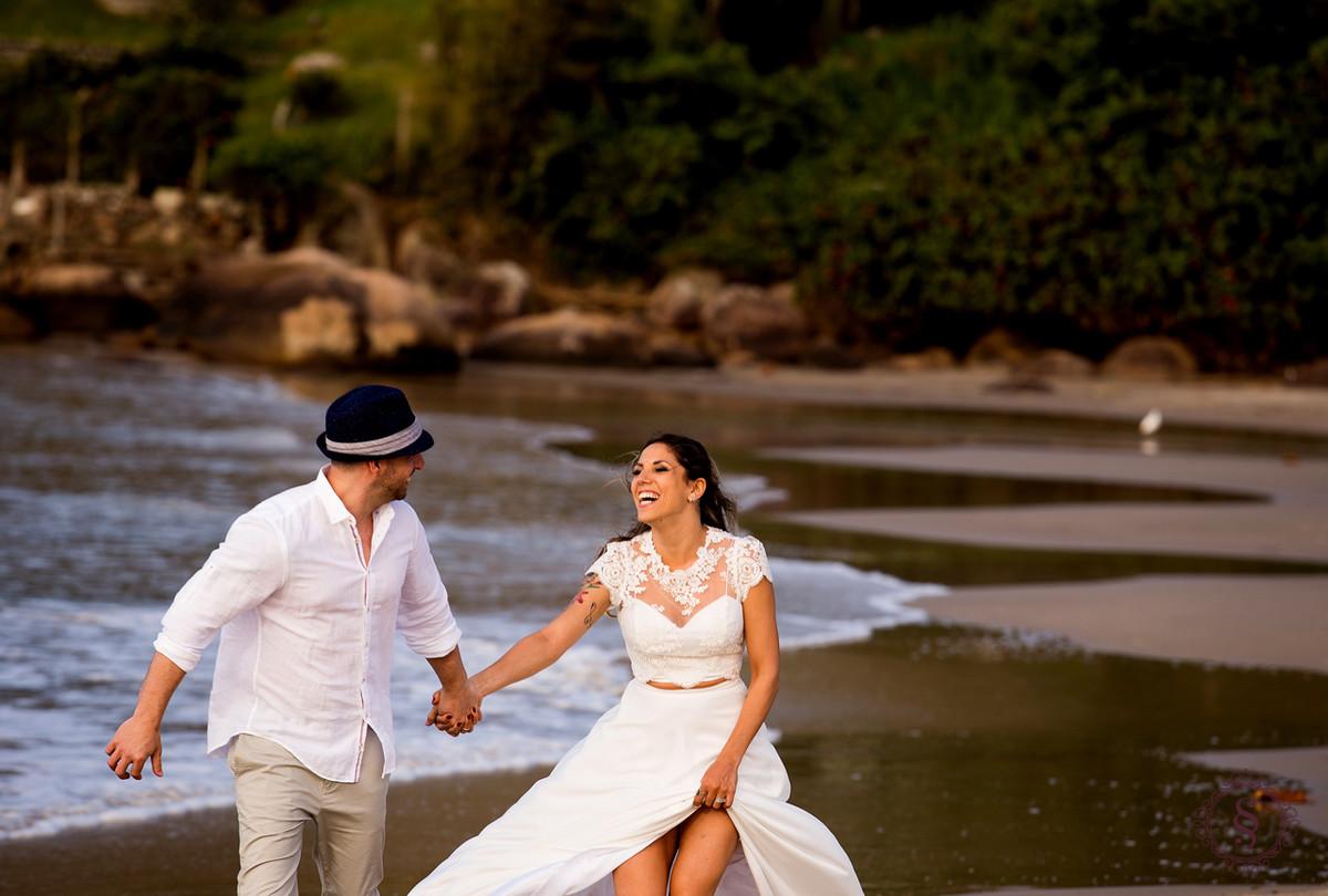 casal de noivos correndo na praia floripa sc