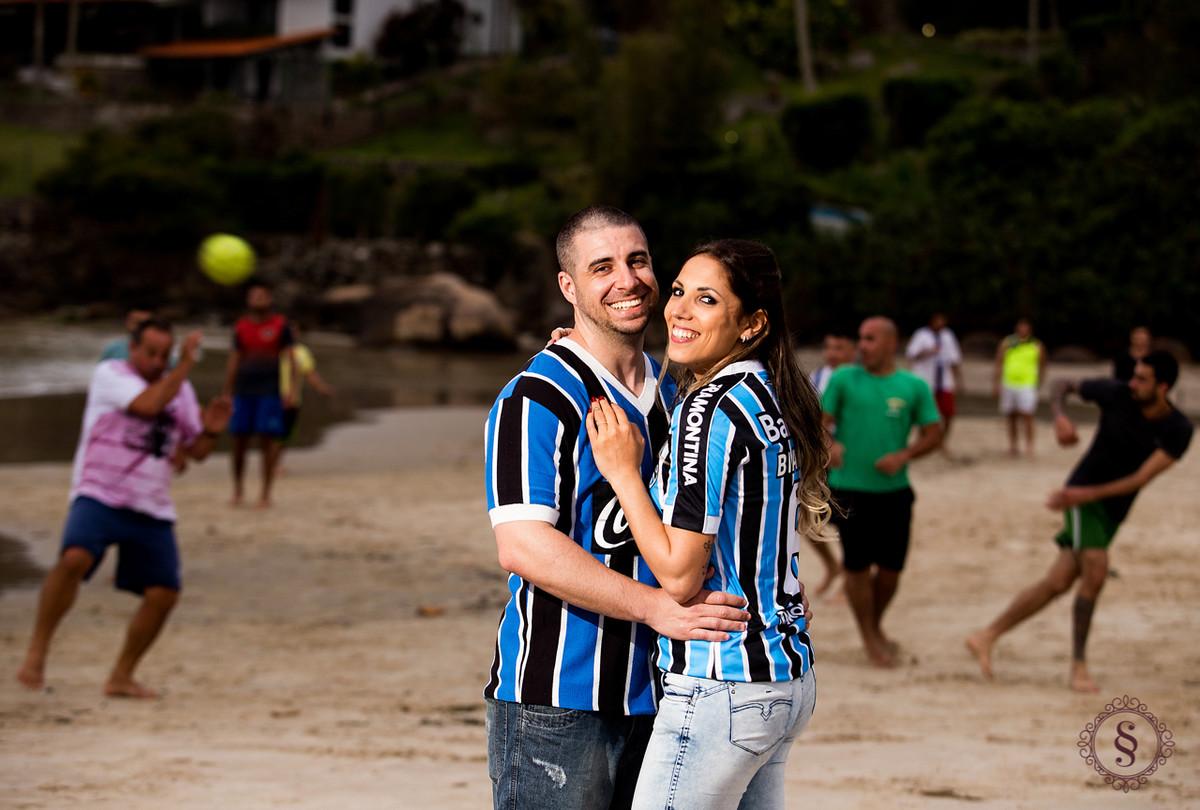 casal com camiseta do grêmio na praia