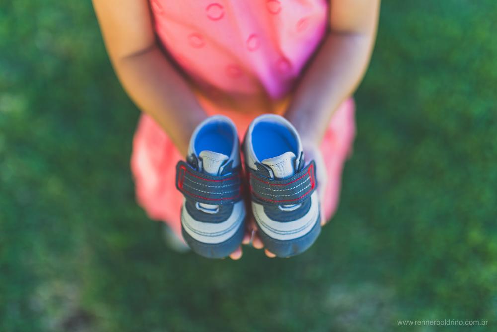 menina segurando sapatinhos de bebê
