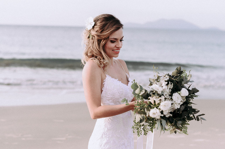noiva na praia olhando para o buquê