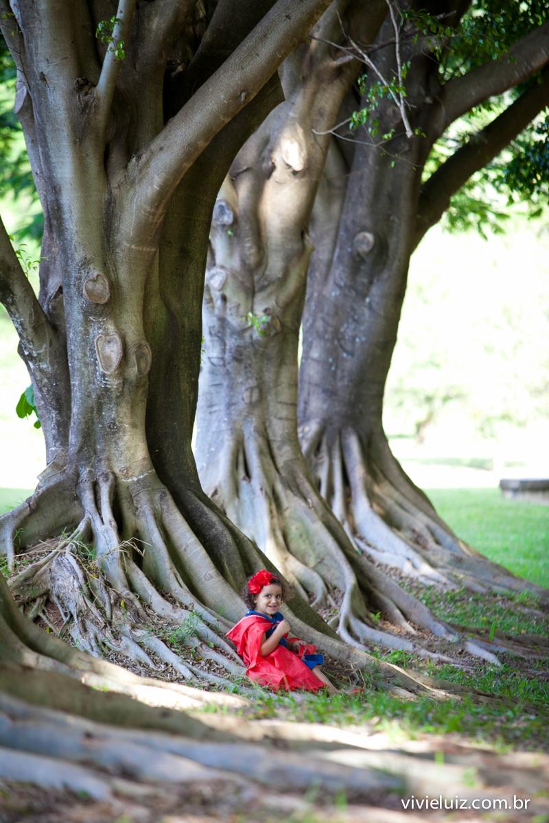 chapeuzinho vermelho sentada em raizes das árvores