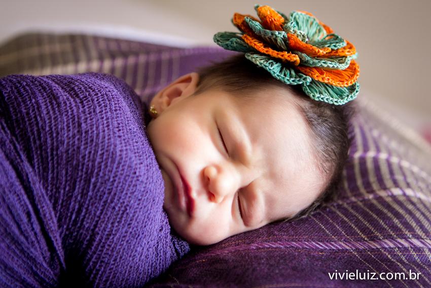 bebe enrolada com paninho roxo e laço de flor colorido