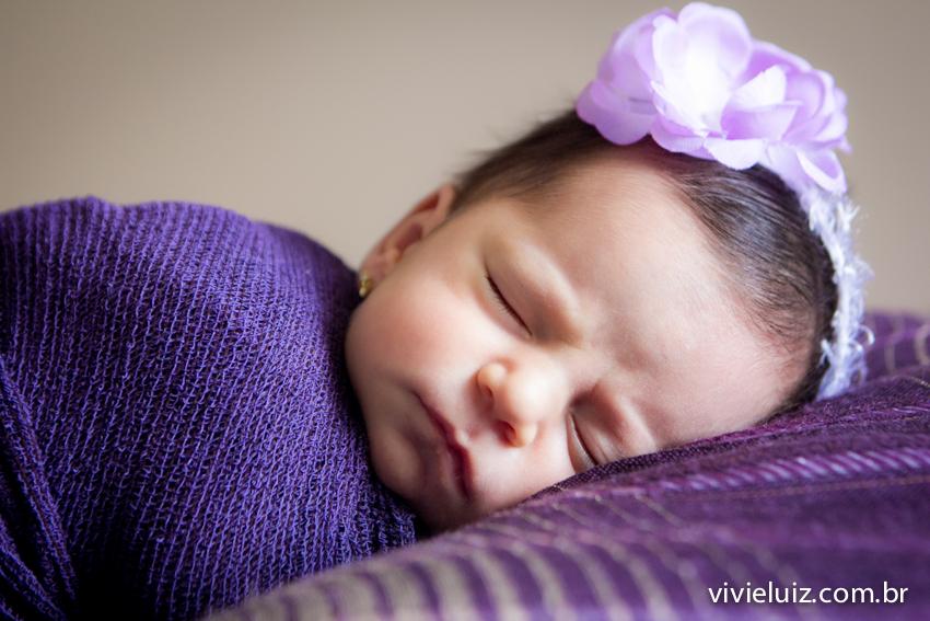 Bebê com flor roxa dormindo