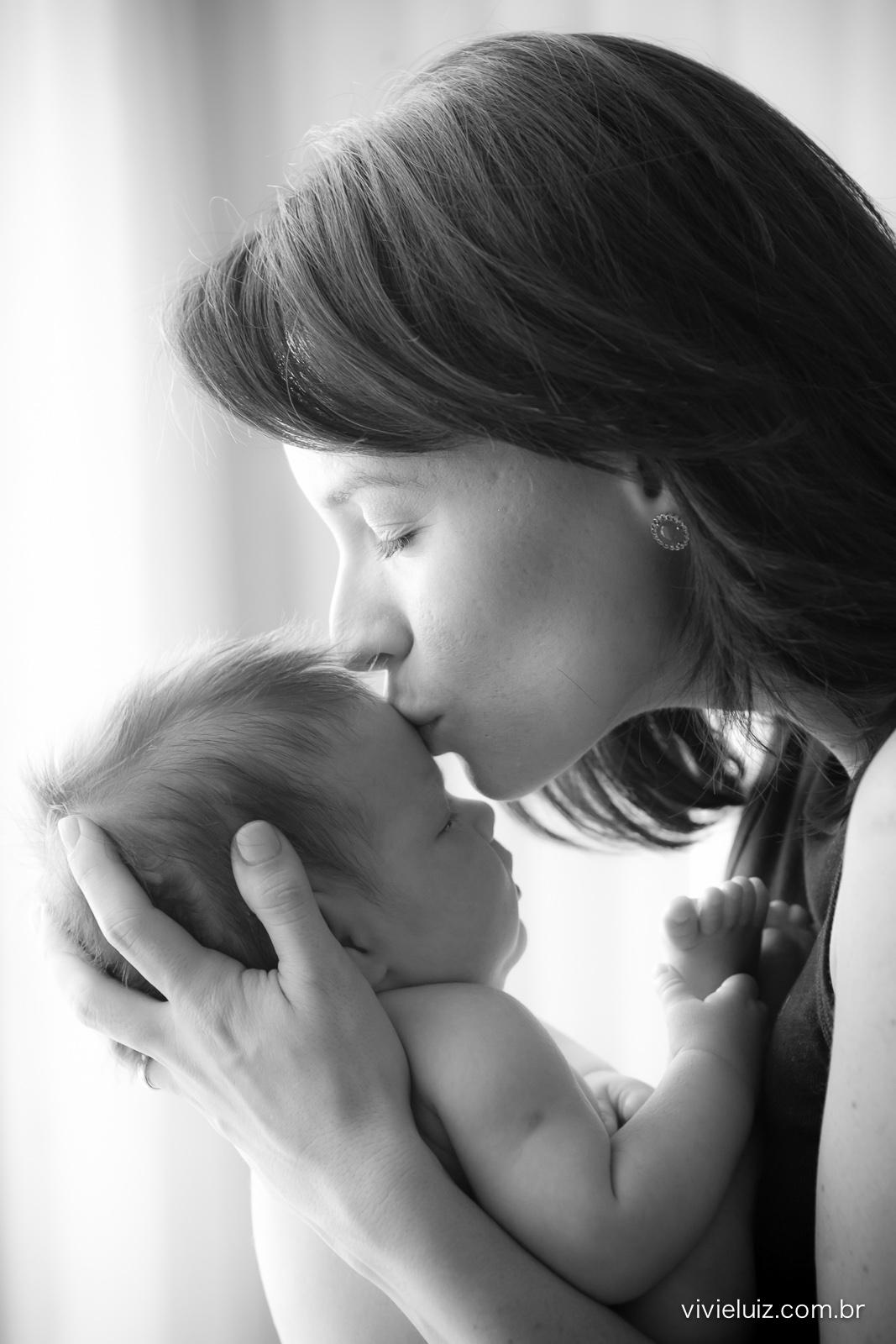 Mãe beijando testa do filho