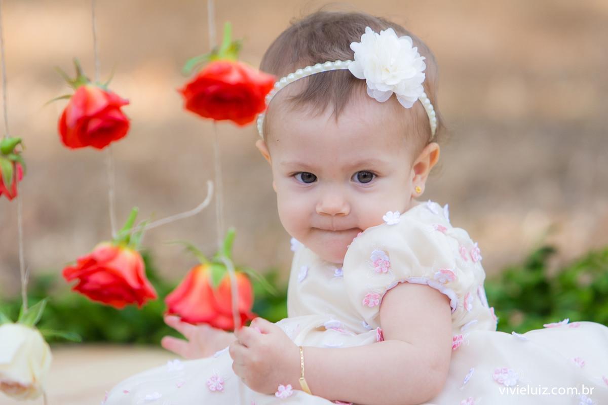 Criança de rosa no fundo de flores vermelhas