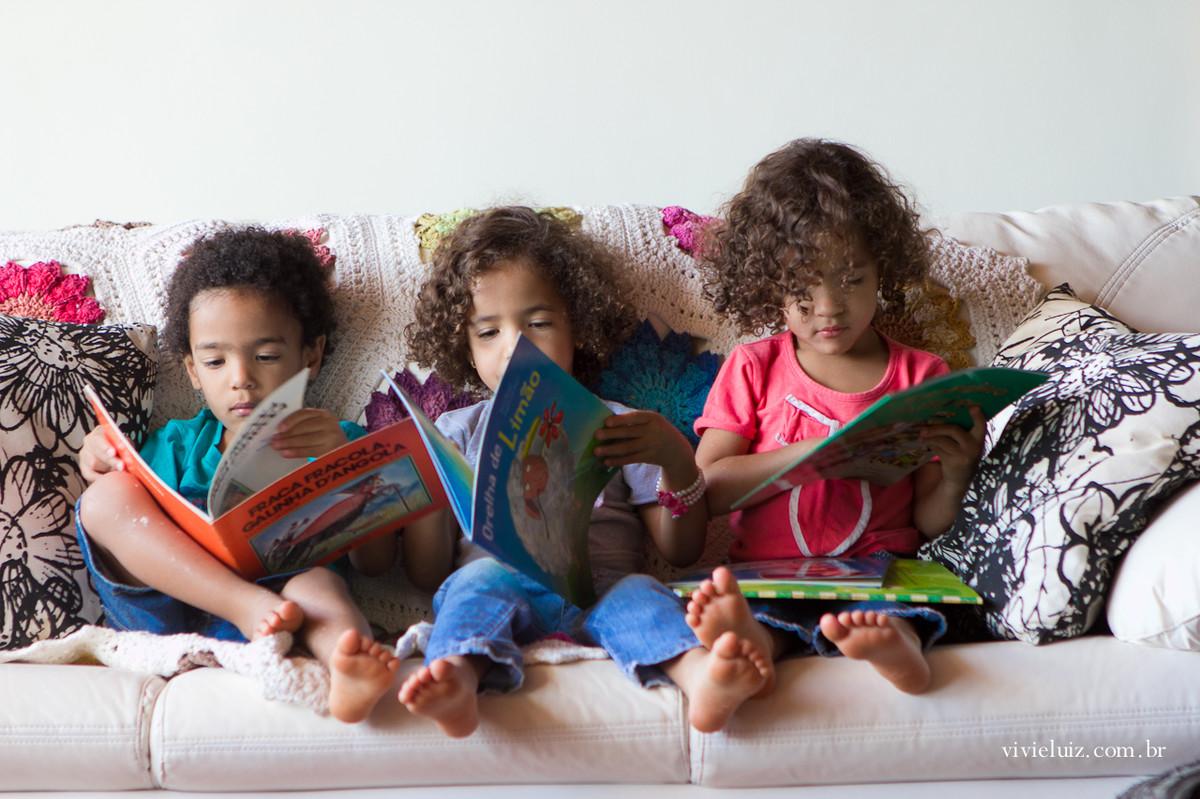 Trigêmeos lendo um livro