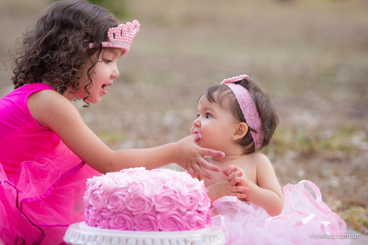 Criança de rosa dando bolo na boca de outra criança