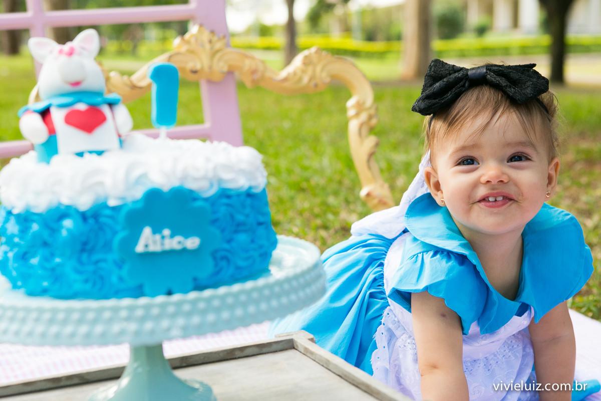 Criança com fantasia da Alice comendo bolo