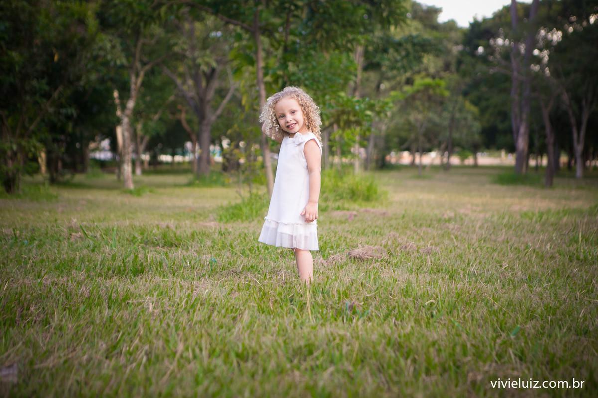 Criança de branco em gramado verde