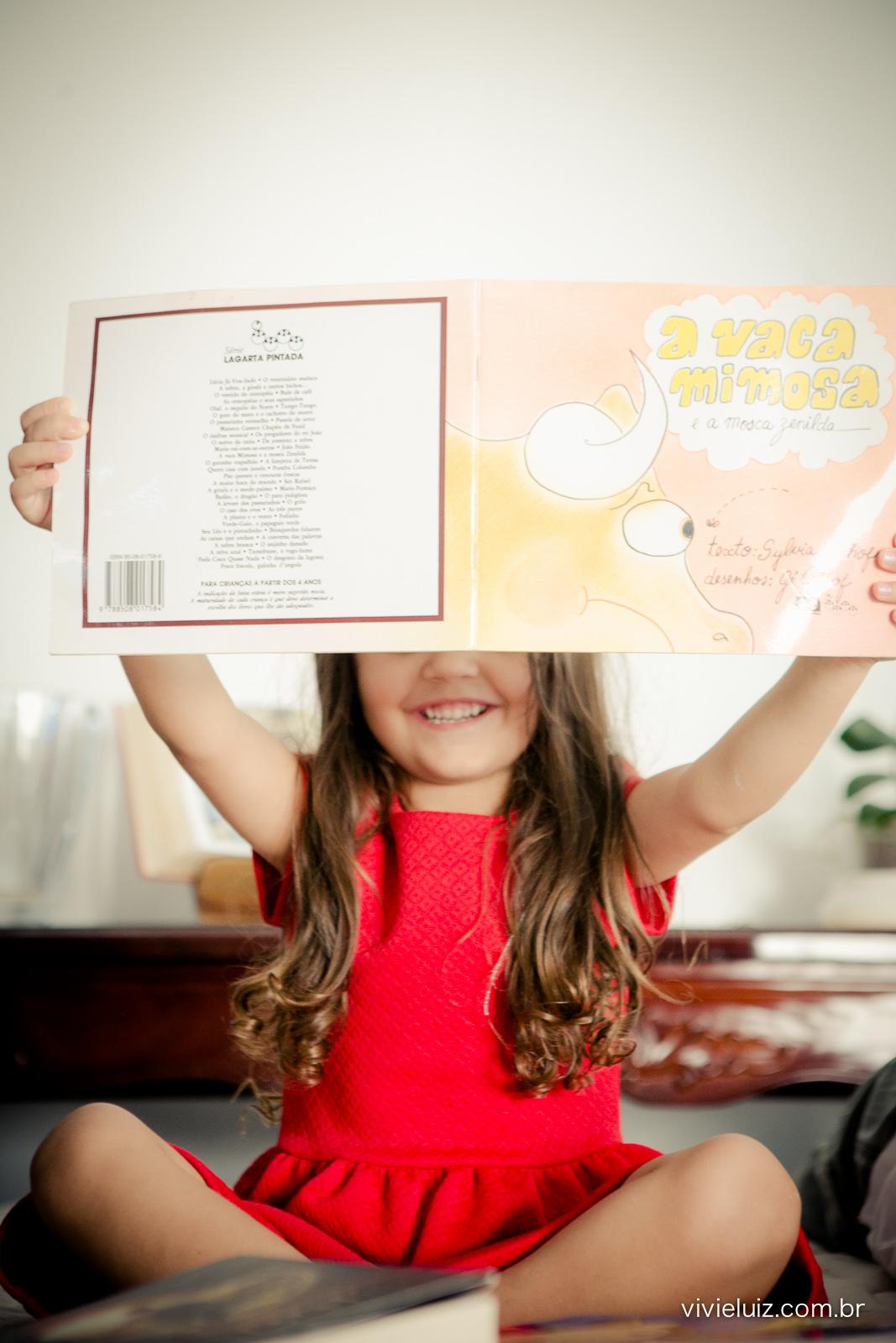 Menina levantando o livro e sorrindo