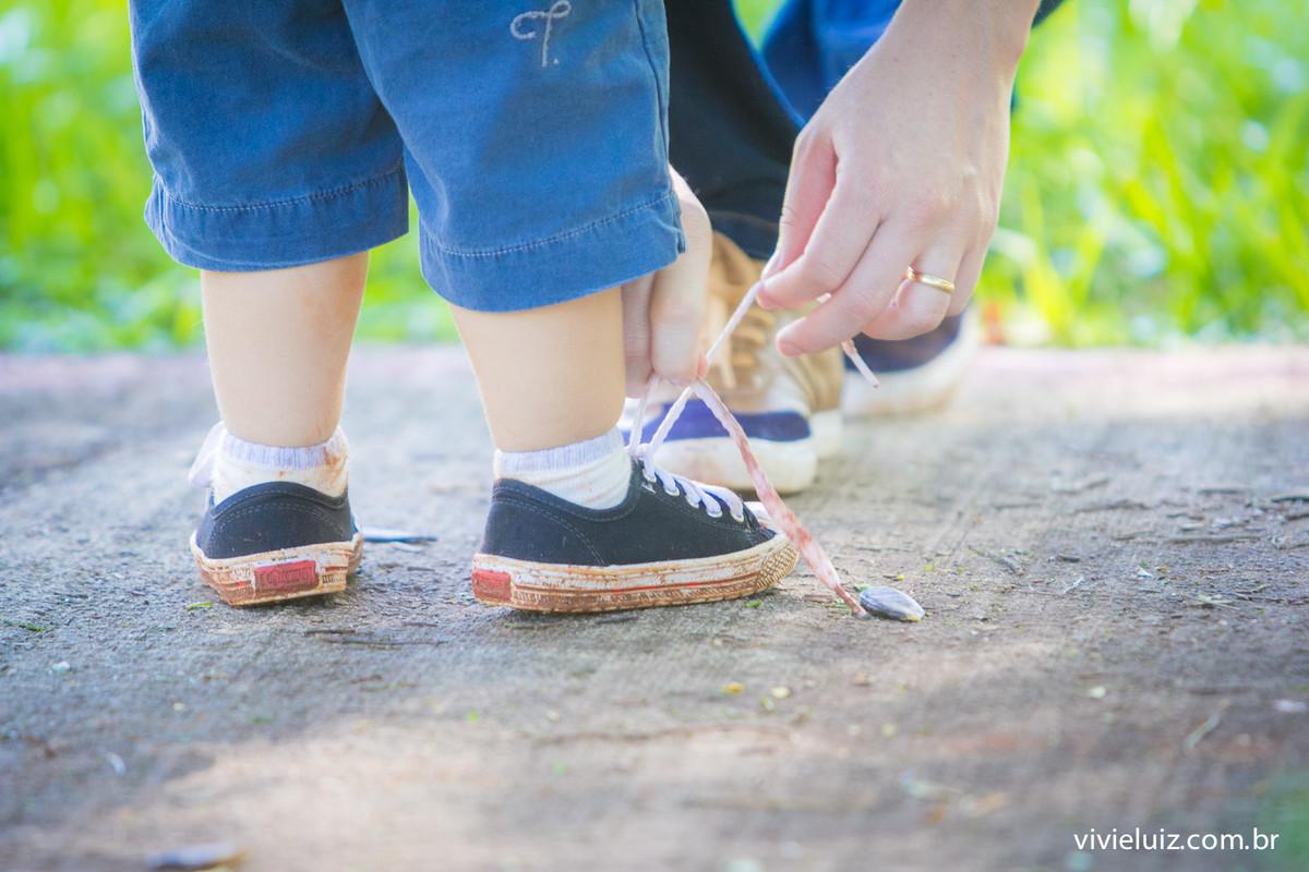 Pai amarrando tênis sujo do filho