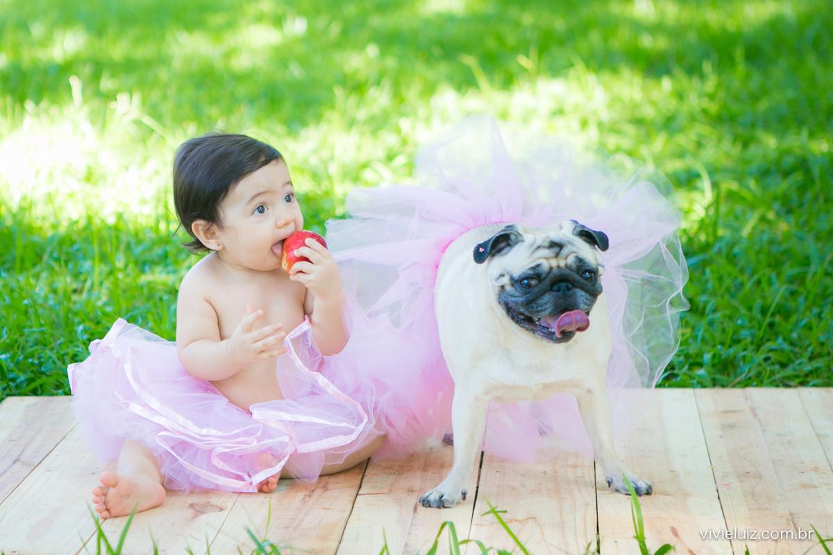 bebe e cachorro de saia comendo maça