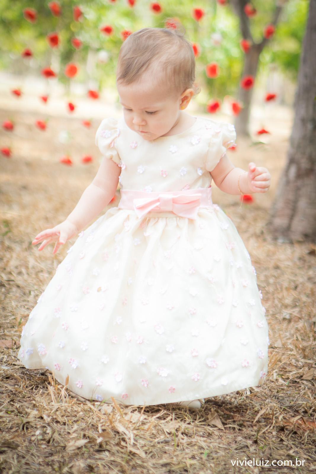 criança com vestido branco e flores ao fundo
