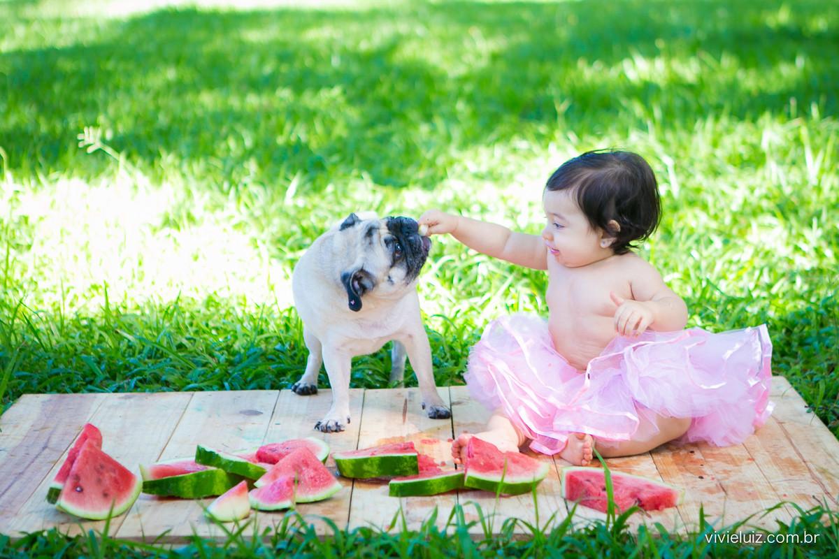 criança dando melancia para cachorro