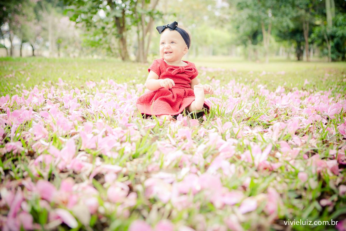menina em campo com flores no chao